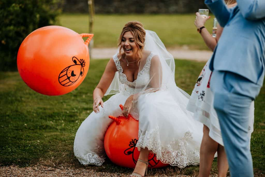 A bride laughs as she plays on a space hopper