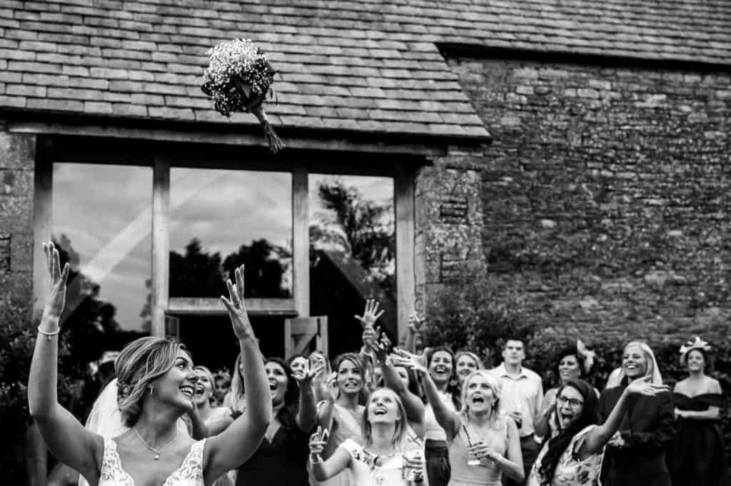 A bride throws her beautiful bridal bouquet to her waiting guests