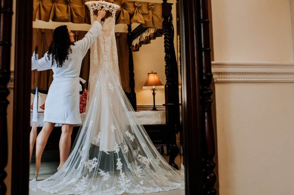 Bride getting her dress ready by Offley Place wedding photographer M and G Wedding Photography