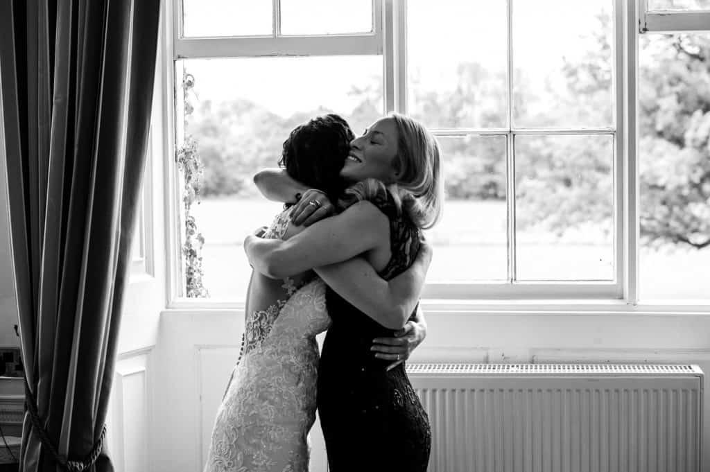Bride hugging her bridesmaid on her wedding day