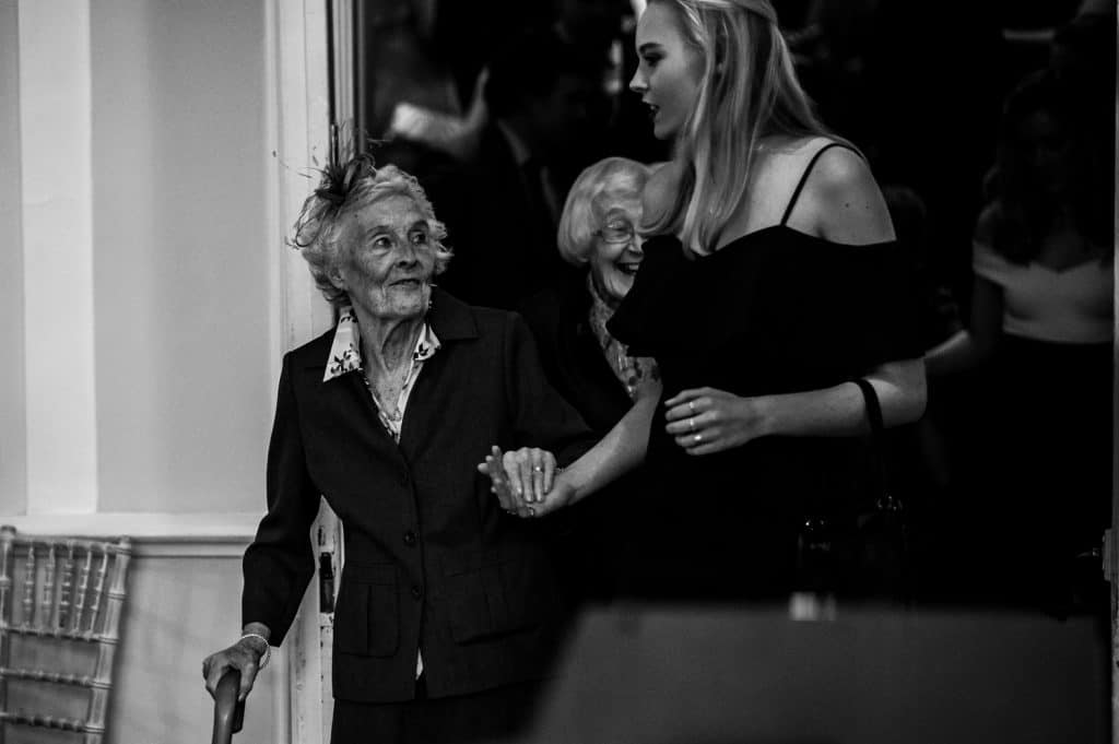 A smiling and happy elderly woman arrives at the wedding ceremony