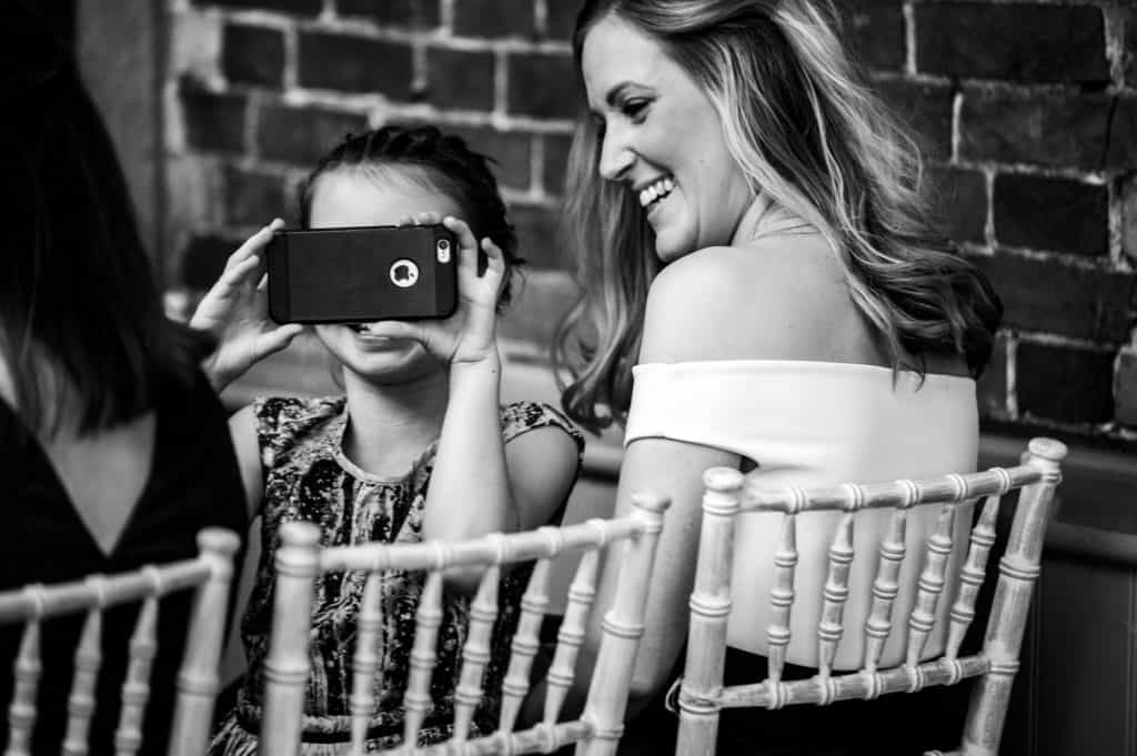 A young girl takes a photograph with a phone