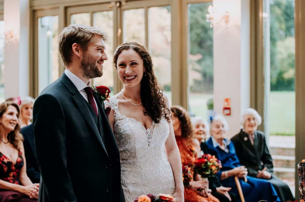 A bride and groom laugh together during their wedding ceremony