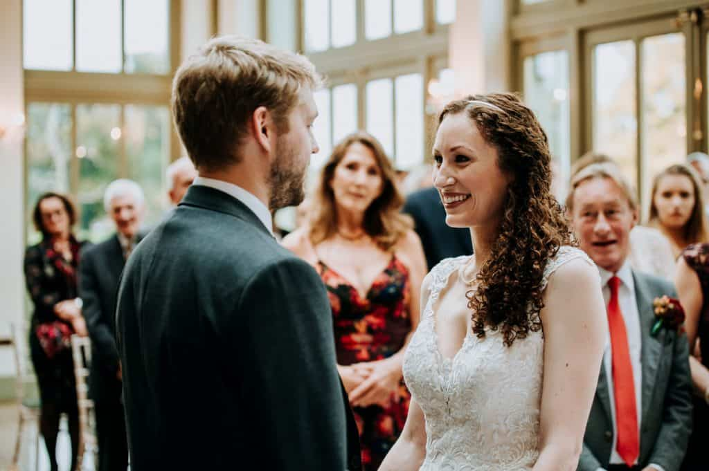 A bride and groom smile at each other during their Offley Place wedding ceremony