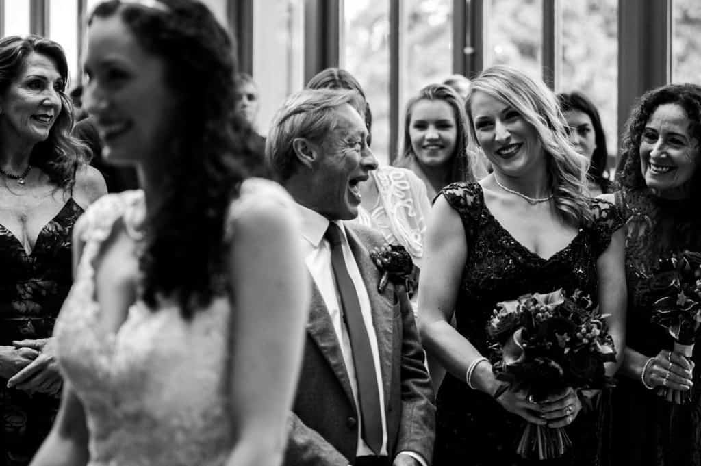 A lovely moment during the wedding service showing guests smiling and laughing captured by M and G Wedding Photography