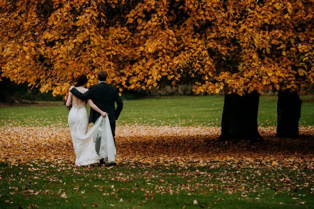 A bride and groom walk through stunning autumnal parkland