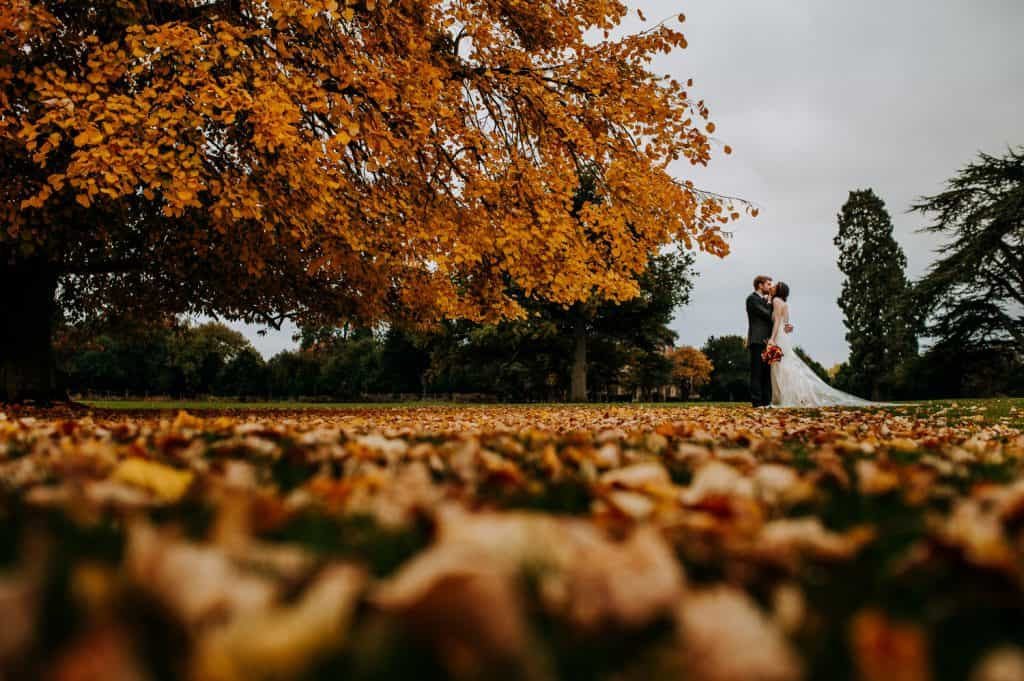 Autumn leaves lay on the floor as a bride and groom kiss in the background at Offley Place wedding venue