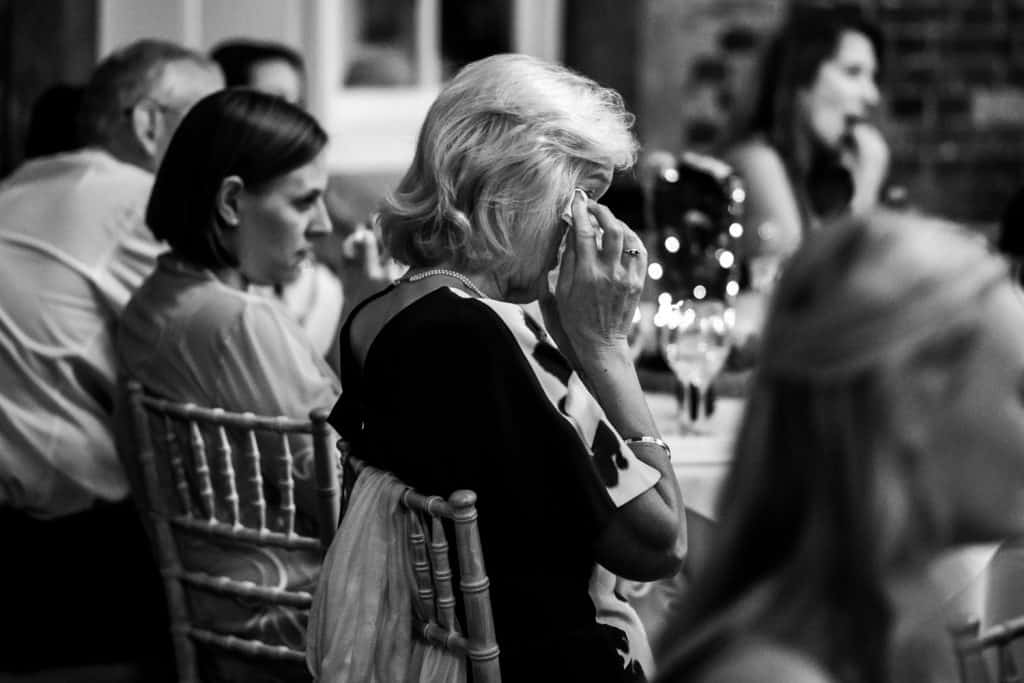 A guest cries during the wedding speeches captured by Offley Place Wedding Photographer M and G Wedding Photography