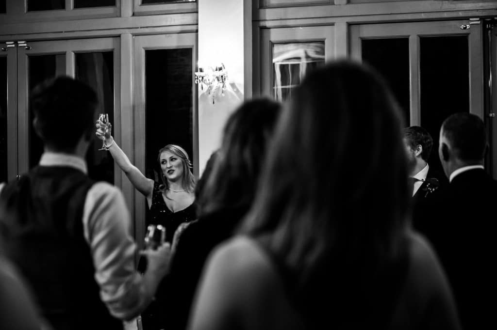 A black and white image of a bridesmaid toasting wedding speeches