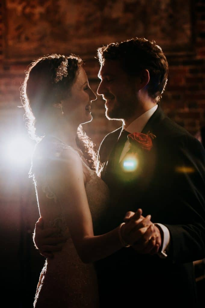 Illuminated by the photographer's flash the bride and groom dance in the ballroom at Offley Place