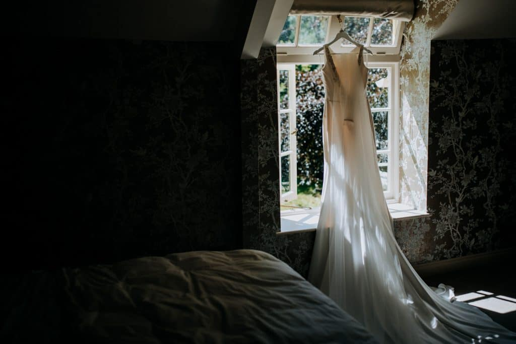 A bridal gown hangs in a window with sunlight illuminating it beautifully and causing dramatic shadows