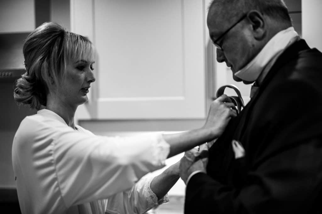 A bride helps her father get ready on the morning of her wedding day