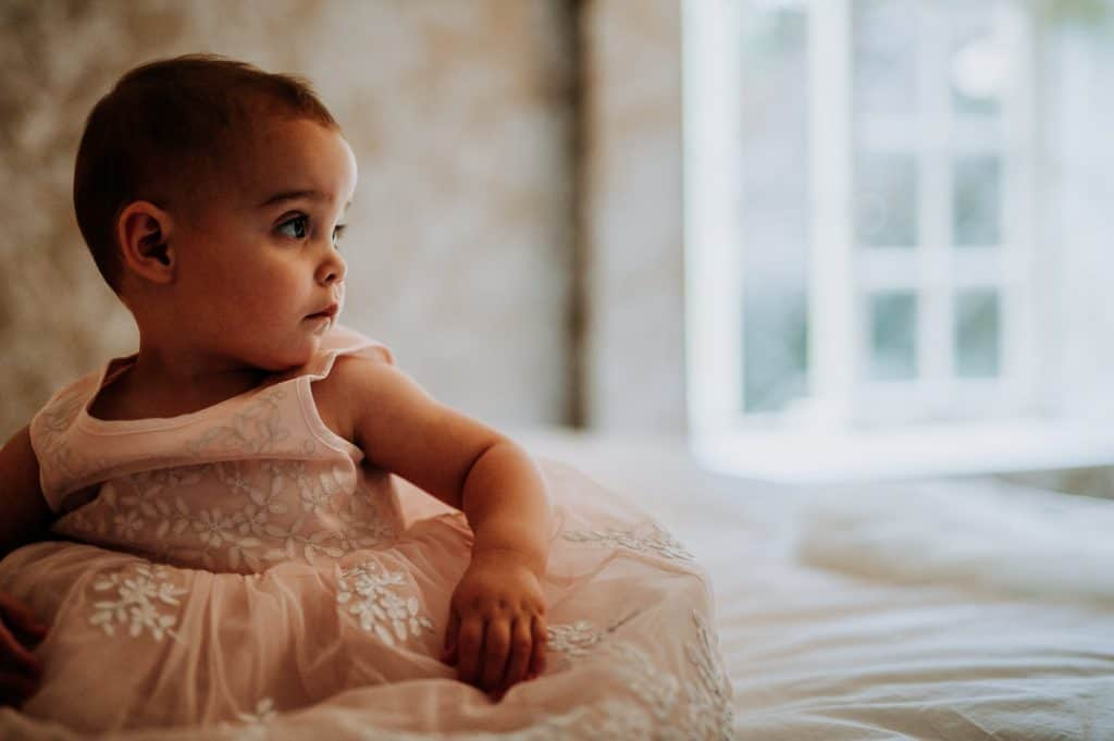 A flower girl sits on a bed and looks to the right