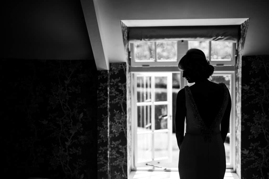 A silhouetted photograph of a bride getting ready on her wedding day by Yorkshire wedding photographer M and G Wedding Photography