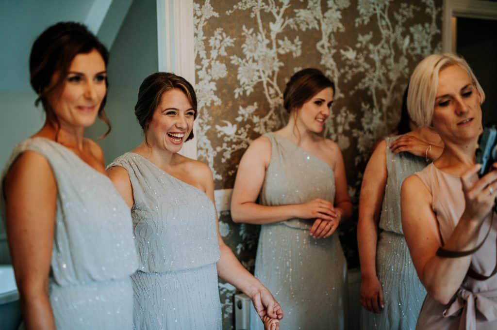 Bridesmaids laughing together as they get ready for a wedding