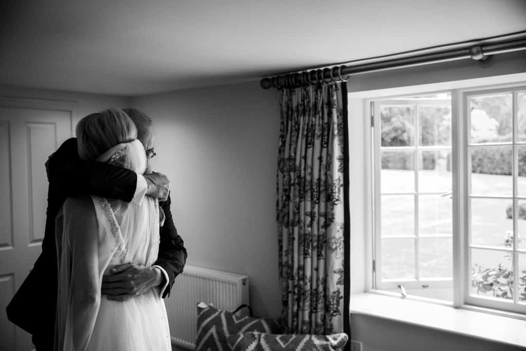 A bride and her father share an emotional hug as he sees her in her bridal gown for the first time