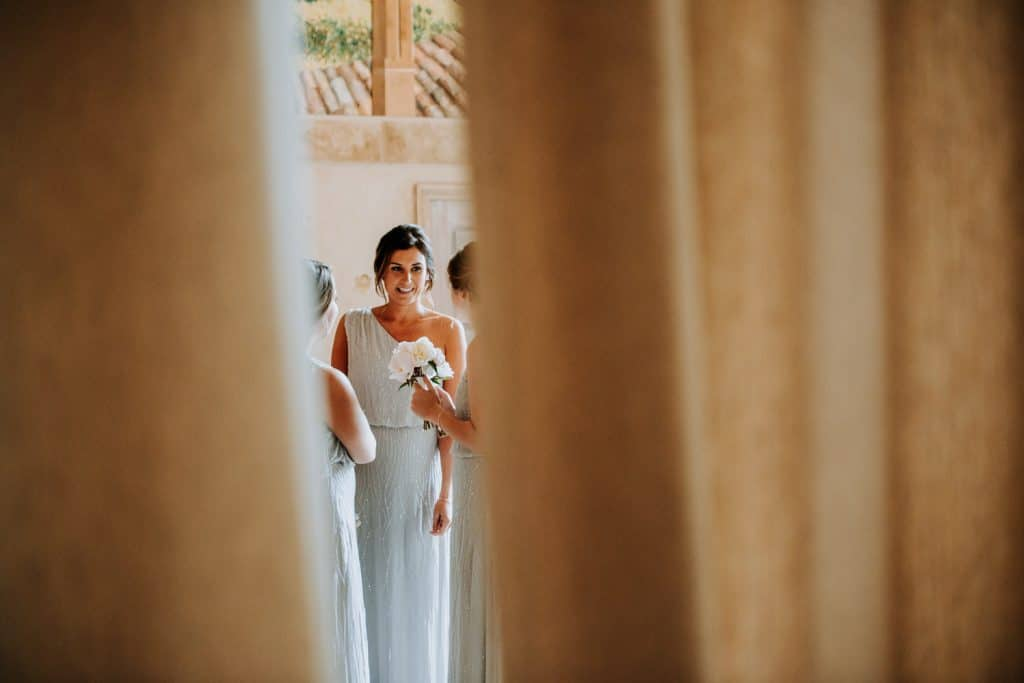 The wedding photographer takes a photograph of a bridesmaid smiling through a large ornate curtain