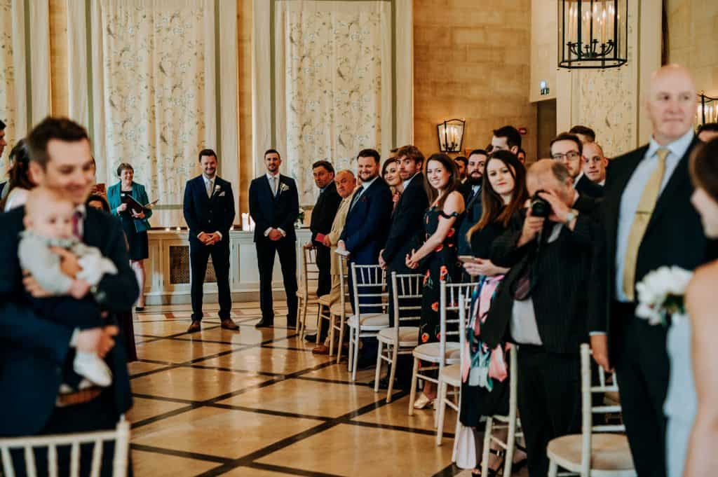 The groom waits for his bride at the end of the aisle smiling captured by M and G Wedding Photography at the Orangery Settrington in Yorkshire