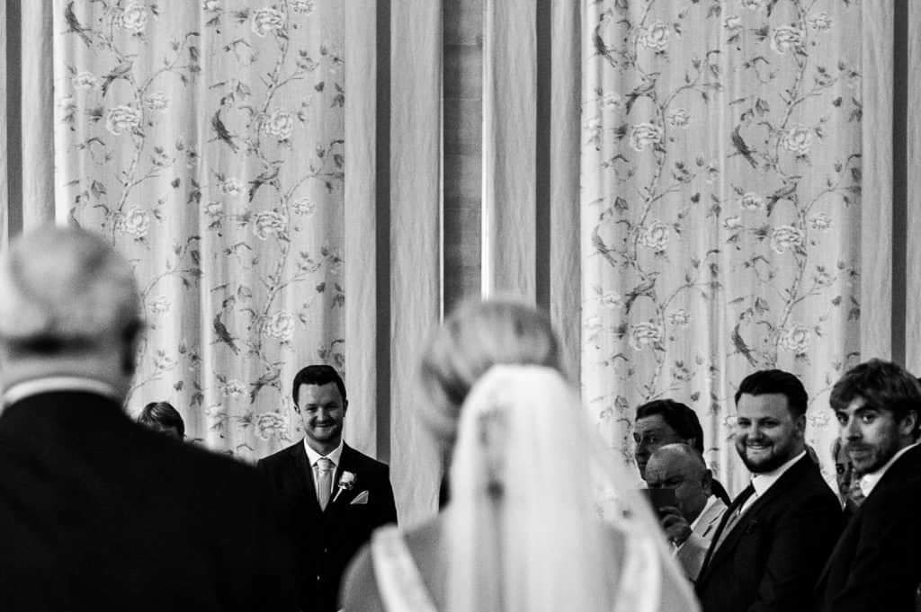 The groom looks back up the aisle as his bride walks towards him so they can get married