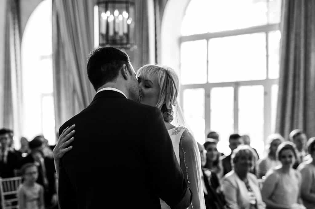 A black and white image by award winning Yorkshire wedding photographer M and G Wedding Photography showing a couple share a romantic first kiss during their wedding service at Orangery Settrington