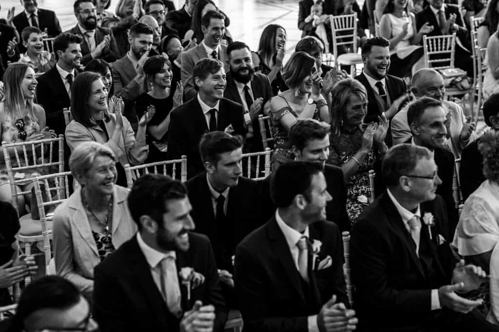 A black and white image by award winning Yorkshire wedding photographer M and G Wedding Photography showing wedding guests cheering and clapping during a wedding ceremony at Orangery Settrington