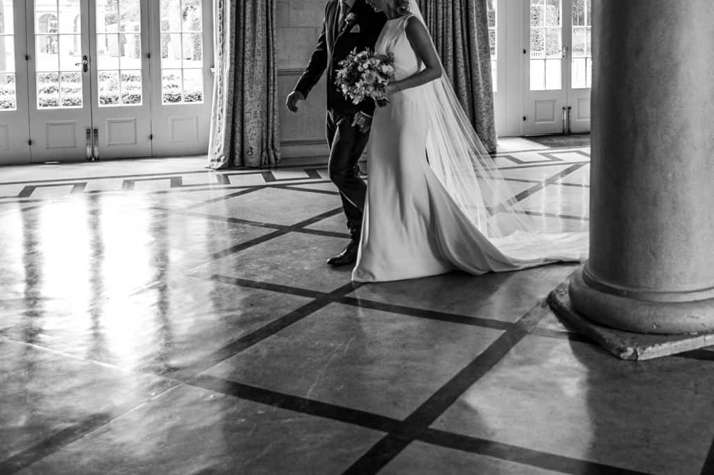 An artistically shot image of a couple walking together through the Yorkshire wedding venue Orangery Settington with shadows and light accentuating the the shapes in the picture