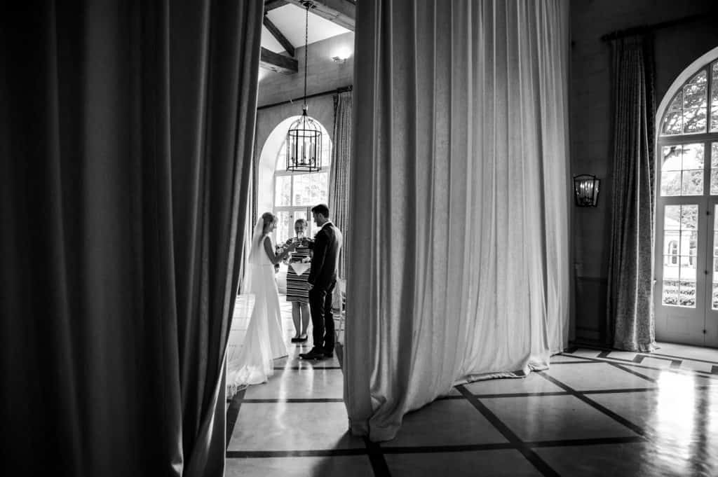 Peering through a grand curtain we see a bride and groom who have just been married being served their first glass of champagne as a married couple