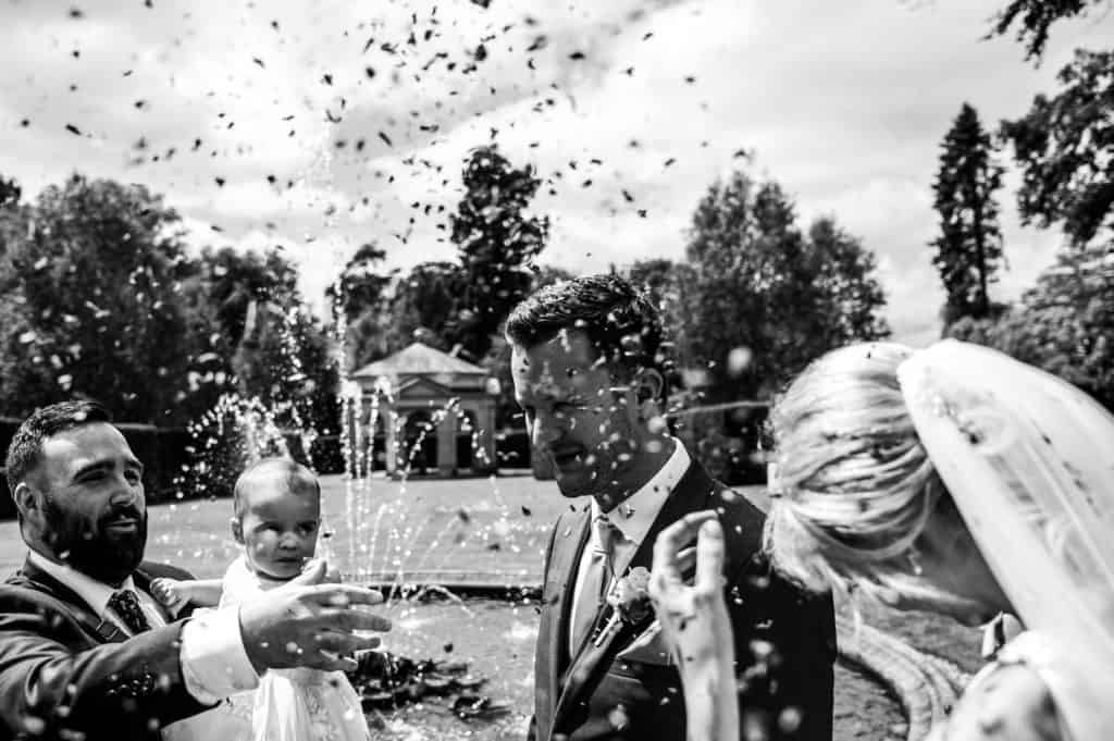 Confetti is thrown over the bride and groom just after a wedding ceremony at Orangery Settrington