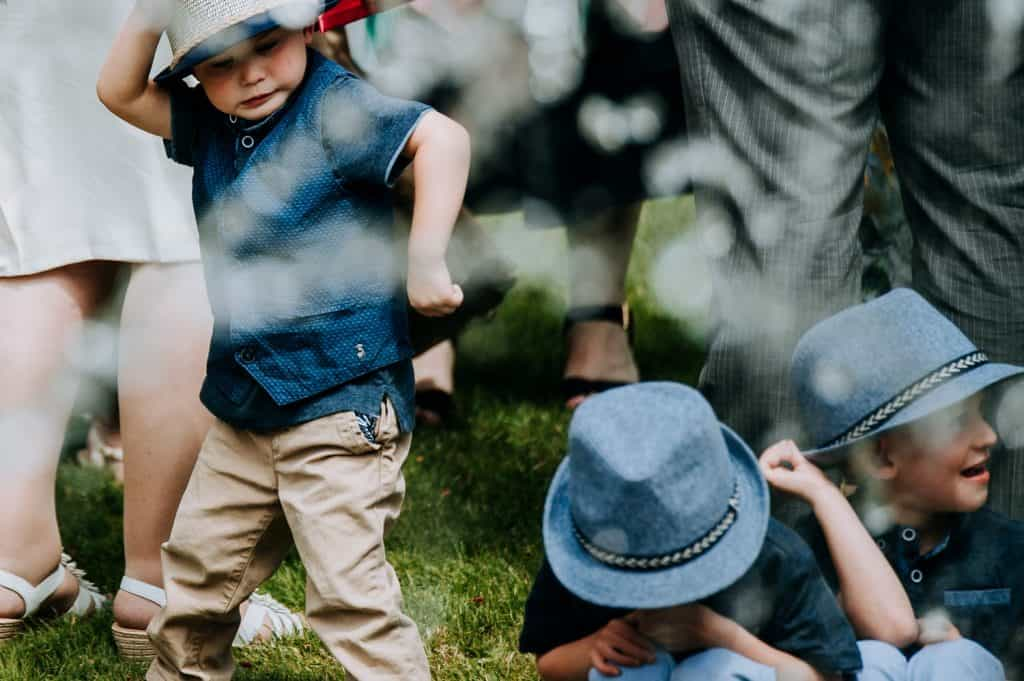 Young wedding guests who are all dressed the same in matching outfits and hats gather around a fountain at the Yorkshire wedding venue Orangery Settrington