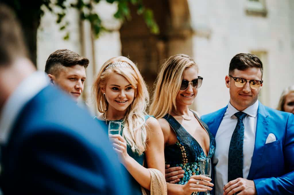 A wedding photograph by award winning Yorkshire wedding photographer M and G Wedding Photography showing wedding guests enjoying drinks outside in the sunshine
