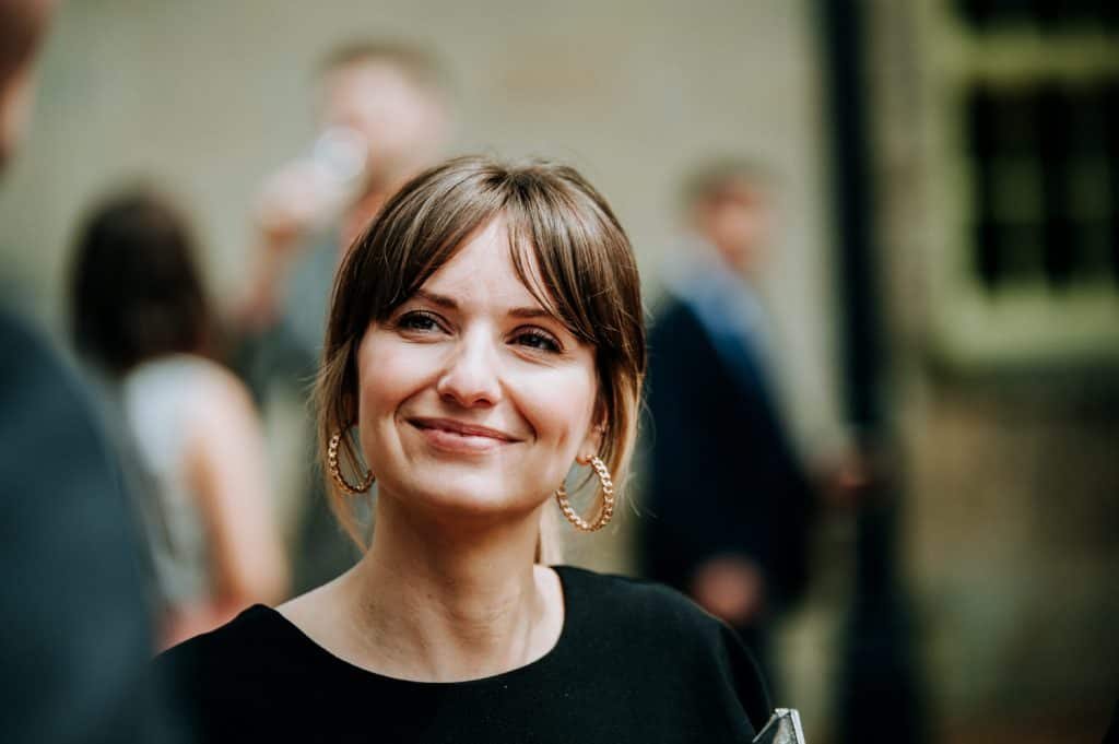 A female wedding guest smiles at the Yorkshire wedding venue Orangery Settrington