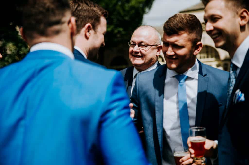 Male wedding guests gather and enjoy a drink at Orangery at Settrington which is an award winning Yorkshire wedding venue