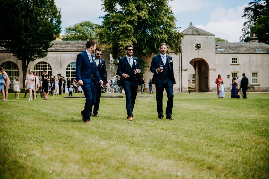 A group of groomsmen stride across a manicured lawn at the Yorkshire wedding venue Orangery Settrington