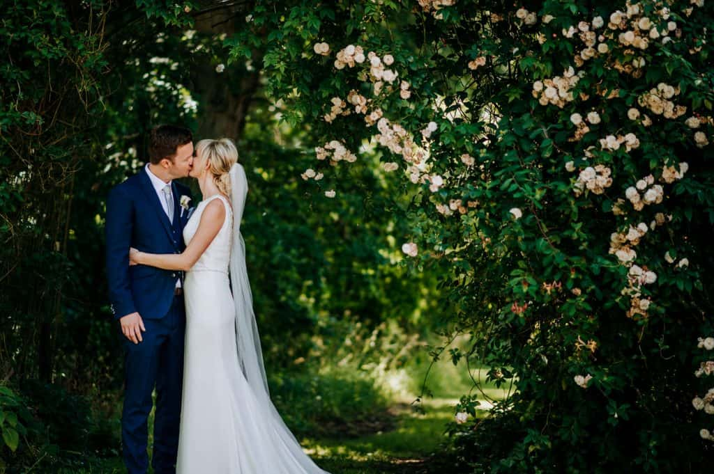 A couple share a kiss on their wedding day within beautiful leafy surroundings