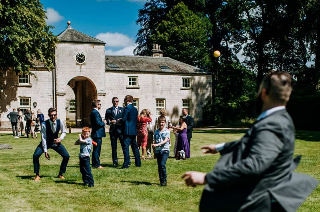 A group of wedding guests play a game of cricket on a wedding day at the Yorkshire wedding venue Orangery Settrington