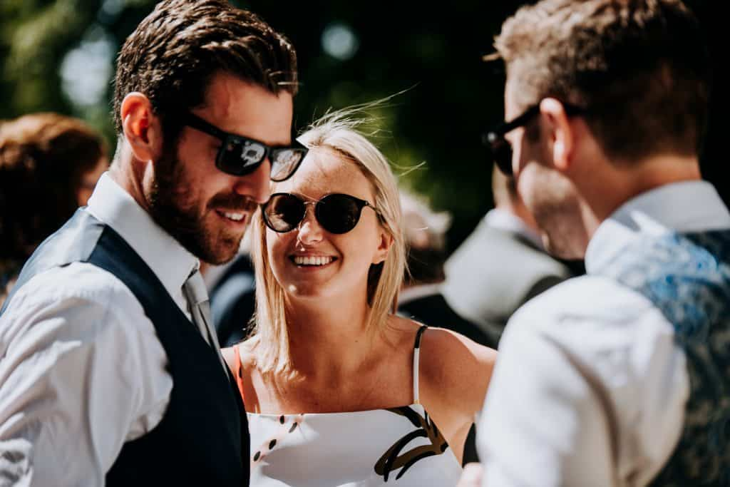 Wedding guests smile and enjoy the sunshine at a Yorkshire wedding