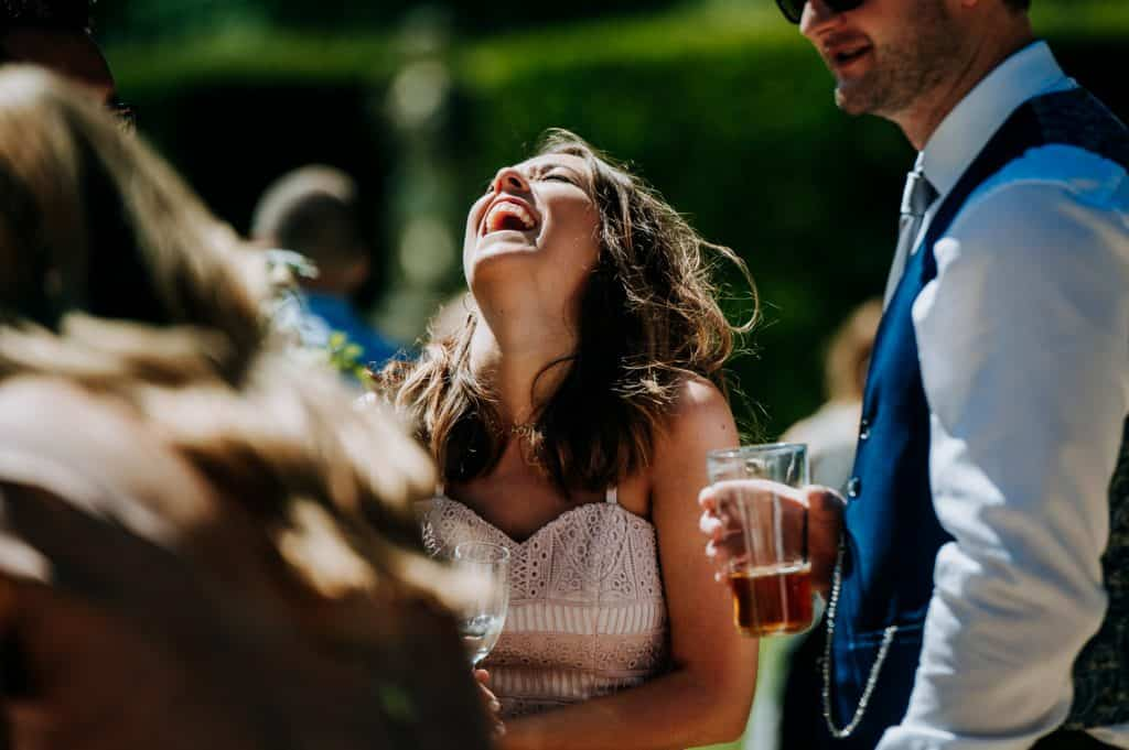 A wedding guest laughs hysterically throwing her head back