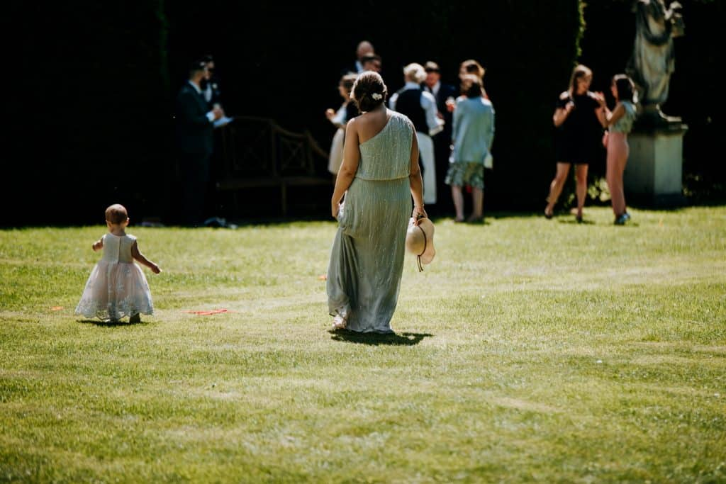 A young flower girl walks across a green lawn at a Yorkshire wedding venue accompanied by an older Bridesmaid