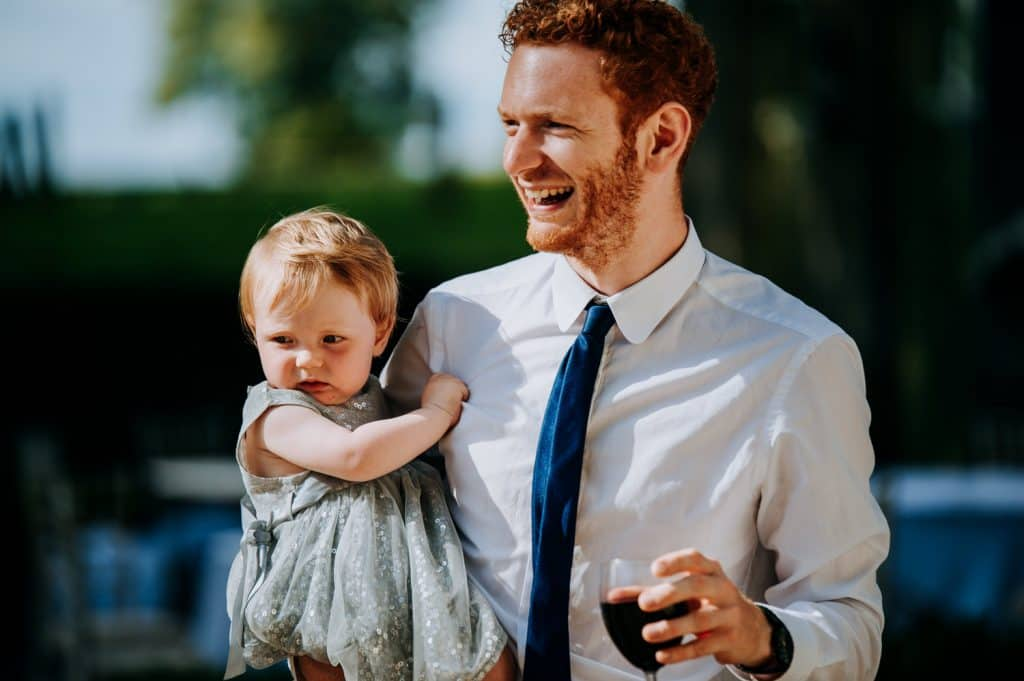 A father holds his young daughter at a wedding while enjoy a glass of red wine