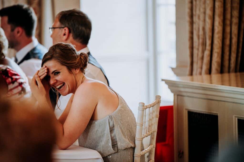 A female wedding guest wearing a pale green dress hides her face and laughs at the wedding speeches captured by Orangery Settrington wedding photographer M and G Wedding Photography