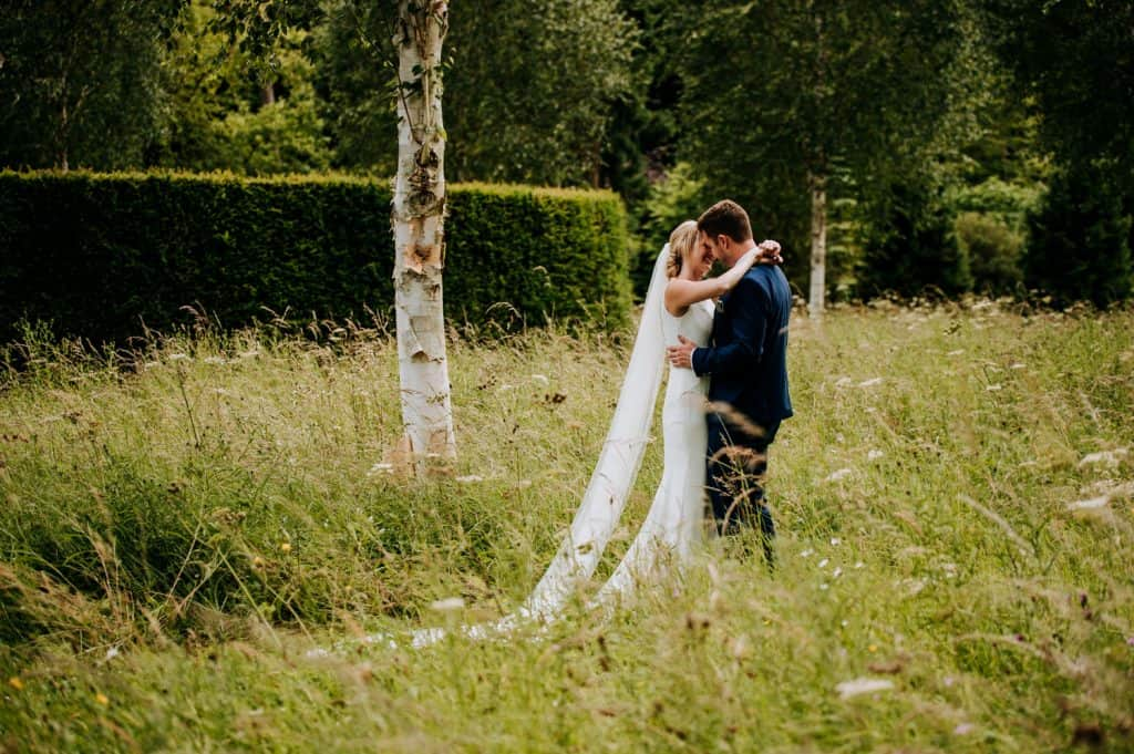 A couple enjoy some romantic time together on their wedding day and are shown here kissing within a meadow
