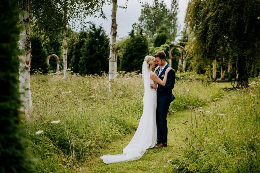 A just married couple kiss each other within their beautiful green wedding venue grounds
