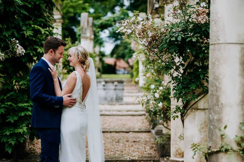 A bride and groom look lovingly at each other within peaceful green surroundings on their wedding day
