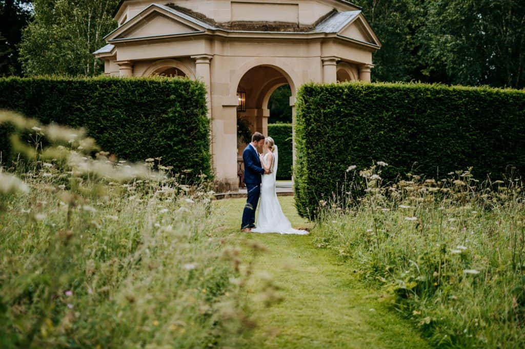 A couple are shown in the centre of the photographic frame kissing one another on their wedding day within a beautiful green landscape