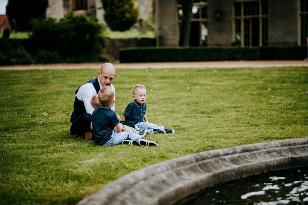 Wedding guests young and old chat together near a pond at a Yorkshire wedding venue