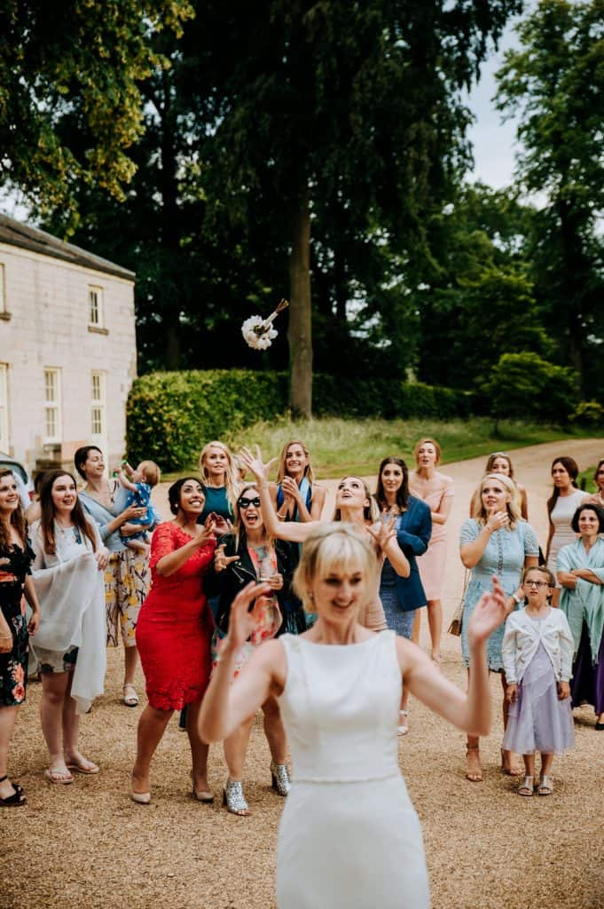 A bride throws her bridal bouquet over her own head to expectant guests behind her