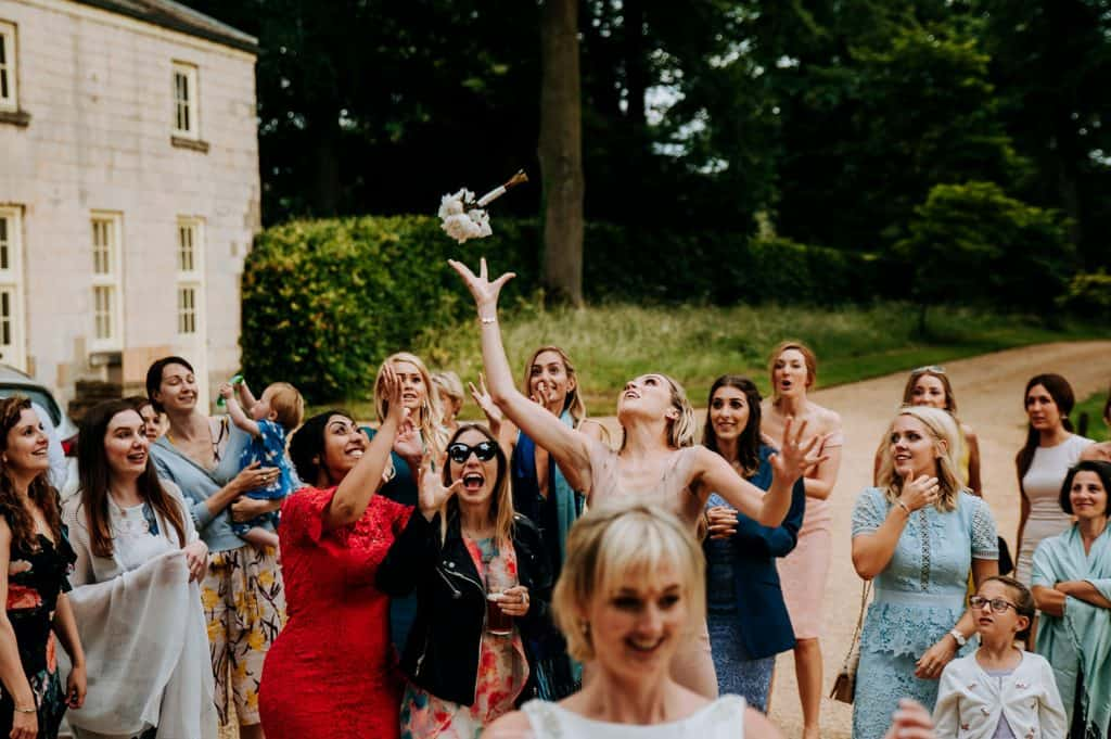 An image showing a female wedding guest just about to catch a bridal bouquet