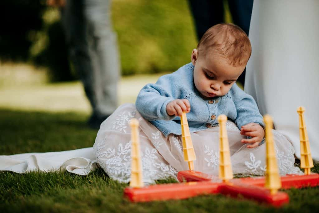 A very young wedding guest plays a garden game quietly on her own