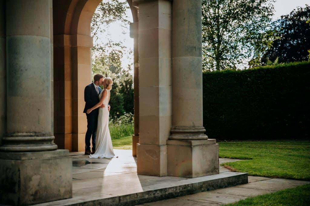 A bride and groom stop to share a kiss framed by a grand arch at Orangery Settrington a beautiful Yorkshire wedding venue