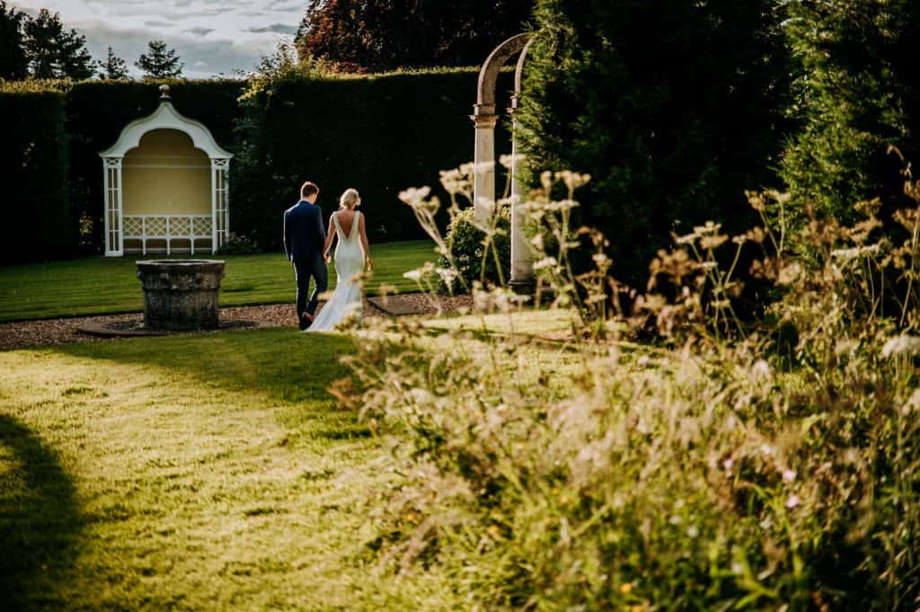 A just married couple take a walk through the beautiful and quiet grounds of their Yorkshire wedding venue